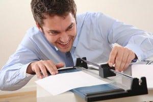 Mann schneidet Papier mit einer Schneidemaschine